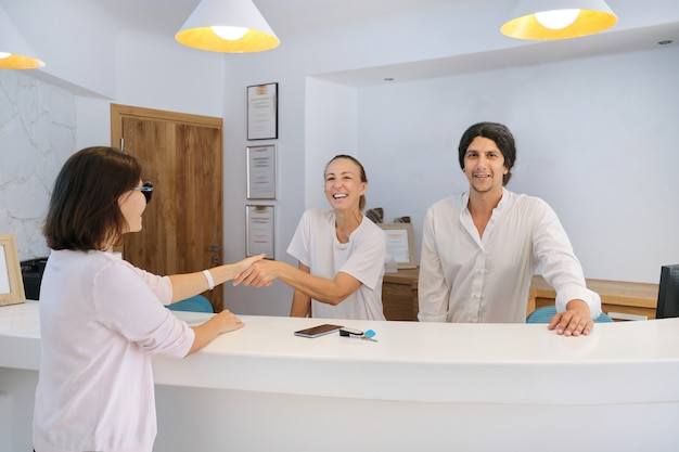Guest checking in hotel, male and female receptionists greeting woman