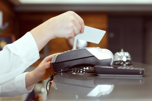 Guest at hotel reception paying with check during check-in