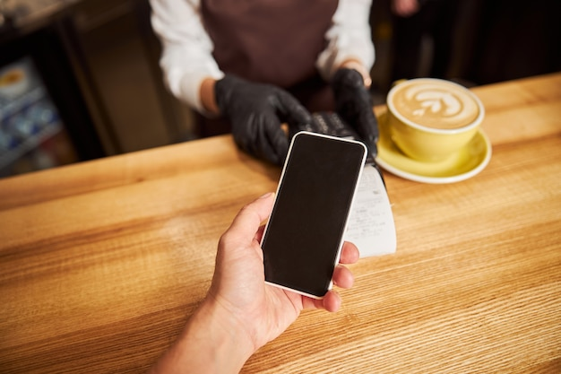 결제를 위해 모바일 애플리케이션을 사용하는 카페의 게스트