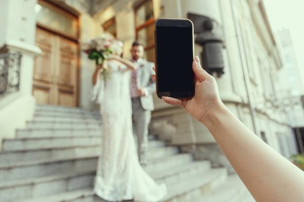 Ospite che fa foto di giovani coppie romantiche caucasiche che celebrano il matrimonio in città. sposa e sposo. famiglia, relazione, concetto di amore. matrimonio contemporaneo