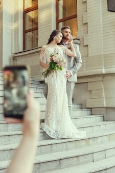Guest making photo of caucasian romantic young couple celebrating marriage in city.