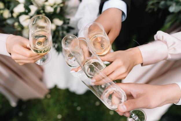 Гости свадьбы с женихом и невестой чокаются шампанским или белым вином.
