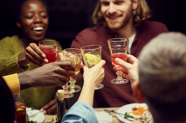 Guests clinking glasses at dinner party