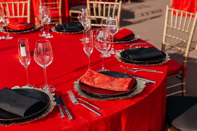Guests table setting in black red and gold style tablecloth plates glasses napkins cutlery