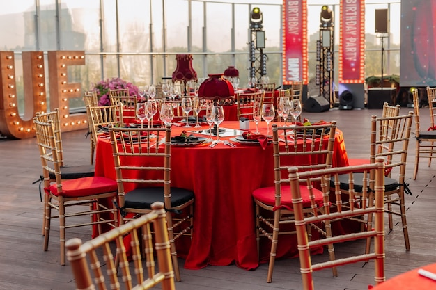 Guests tables and chairs for banquet in black red and gold style elegant party on roof outdoor