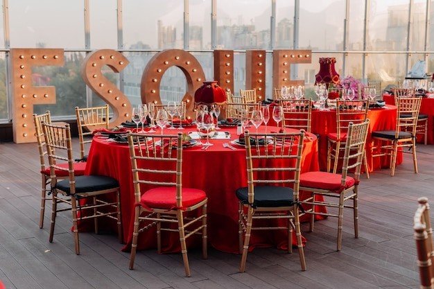 Guests tables and chairs banquet in black red and gold stylethemed party celebration on the roof
