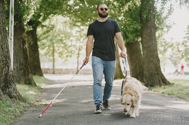 Guide dog helping blind man in the city. handsome blind guy have rest with golden retriever in the city.