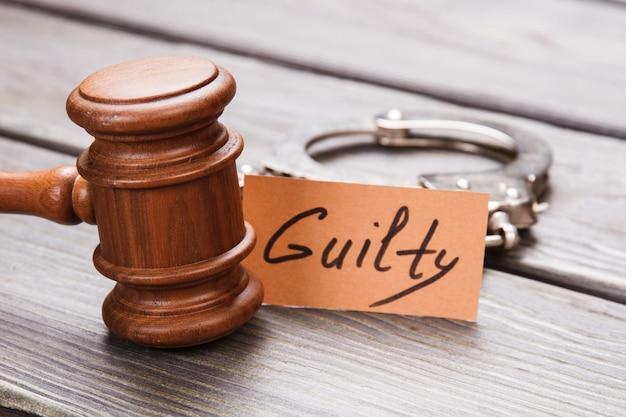 Концепция виновности и преступления. крупным планом коричневый деревянный молоток с наручниками на деревянном столе.