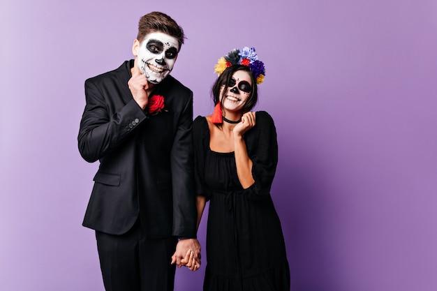 Il ragazzo colpevole e la sua ragazza stanno cercando di sorridere dolcemente. ritratto di donna con accessori luminosi e uomo in abito classico scuro in posa con il trucco per halloween.