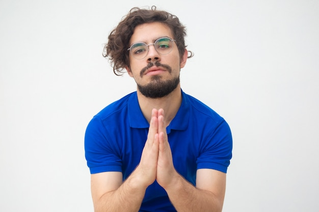 Guilty guy keeping hands in pray gesture