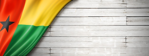 Guinea bissau flag on old white wall. horizontal panoramic banner.
