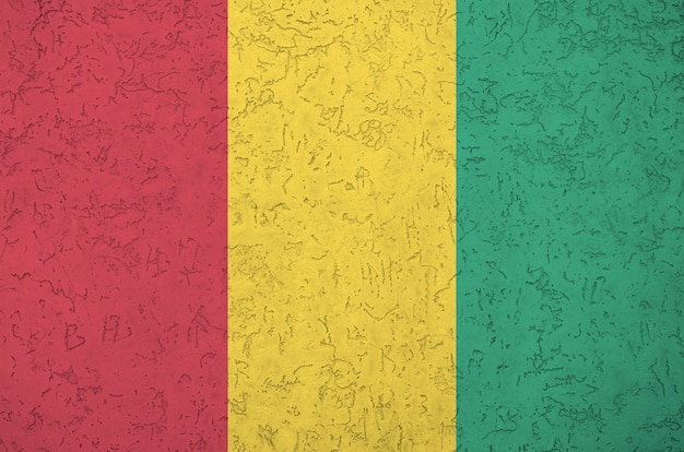 Guinea flag depicted in bright paint colors on old relief plastering wall.