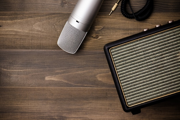 Guitar amplifier and microphone on wooden background. vintage effect style.