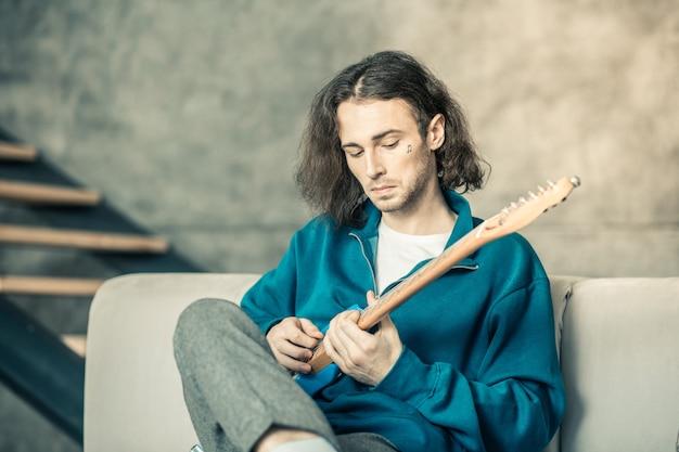 ギターとアンプ。頬にタトゥーを入れた好奇心旺盛な若い男が、毎日の繰り返し中に楽器を設定している