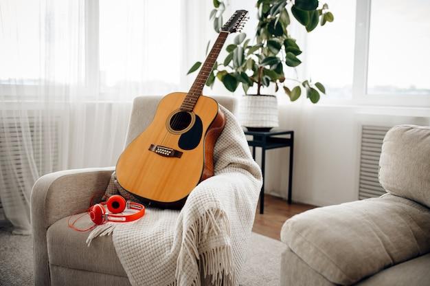 家の白い肘掛け椅子にギターとヘッドフォン、誰もいない。部屋の音響楽器とイヤホン、音楽愛好家のコンセプト