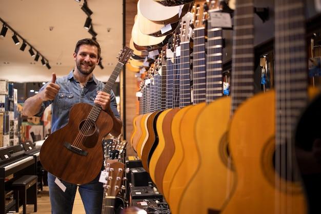 Покупатель гитары держит палец вверх в музыкальном магазине.