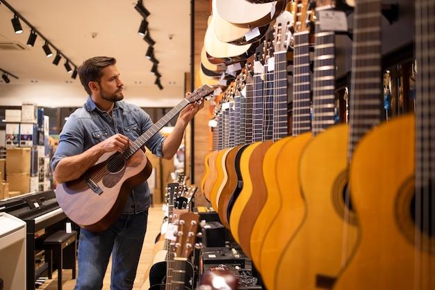 Покупатель гитары тестирует новую гитару, которую он собирается купить в музыкальном магазине.
