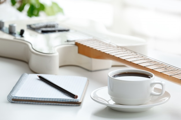 Guitar, coffee, notepad and pencil