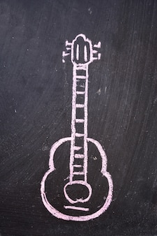 Guitar drawn on a black slate