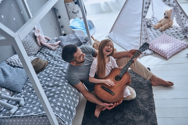 Guitar fun. top view of young father teaching his little daughter to play guitar and smiling while sitting on the floor in bedroom