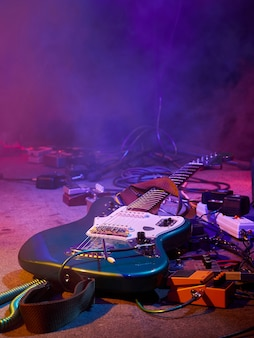 Guitar and guitar equipment lie on stage in fog and smoke in purple, blue and orange lighting.