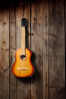 The guitar hanging on the old wooden wall