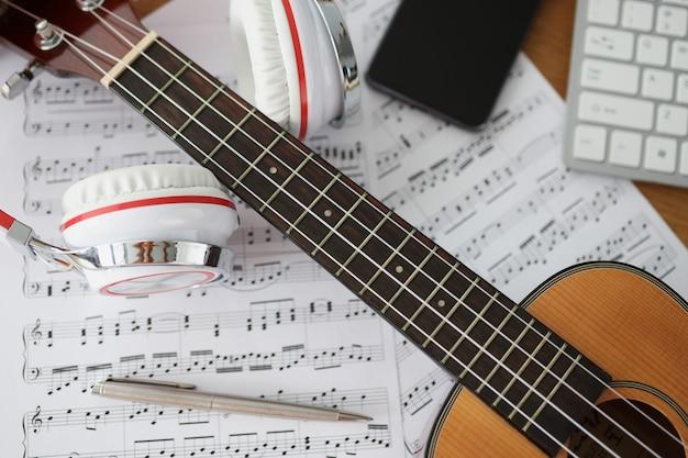 Гитарные наушники и музыкальные ноты на классных столах и концепции обучения музыке