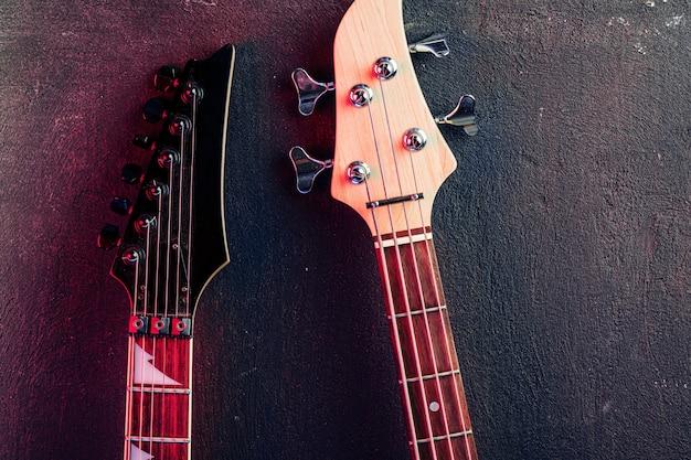 暗い背景上のチューナーとギターのヘッドストックをクローズアップ