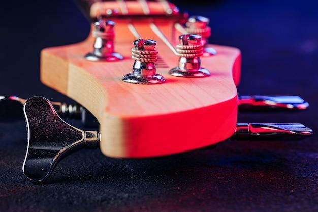 暗い背景にチューナーとギターのヘッドストックをクローズアップ