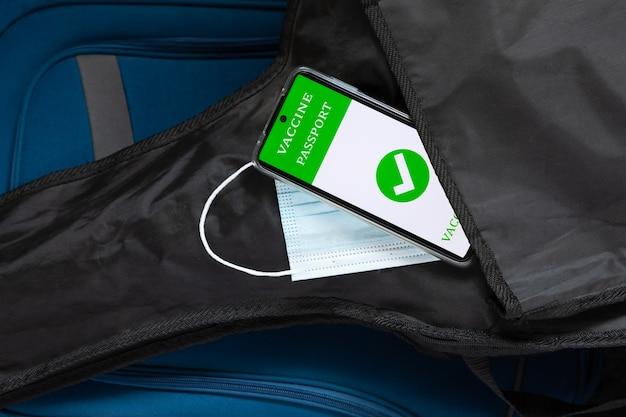 黒いケースに入ったギター、旅行かばんのハンドバッグ、保護用フェイスマスク、携帯電話のデジタルワクチンパスポートid。新しい通常の旅行の概念