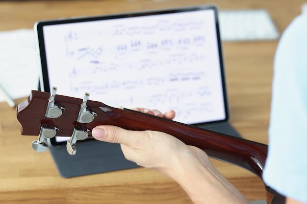 Гитара в женских руках на фоне планшета с музыкальными нотами, преподавание музыки удалено