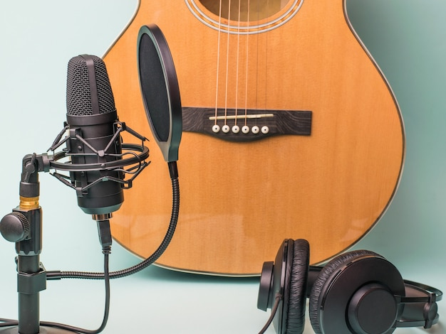 Guitar, microphone and headphones on a blue surface
