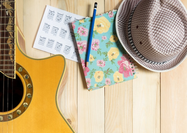 Guitar music and summer hat music writing on wooden background.