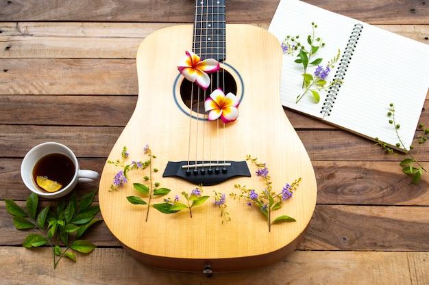 ギター、ノート、木製のテーブルでホットコーヒー