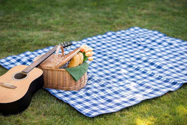 Guitar and a picnic basket on a blanket