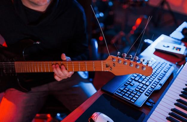 ギター奏者はスタジオの屋内でレコーディングセッションを行っています。