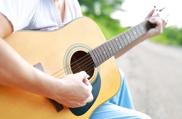 Guitar player playing song in the nature.