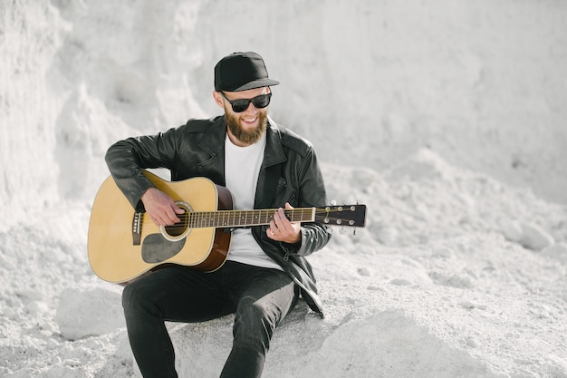 Гитарист поет снаружи. битник гитарист с бородой и черной одежде