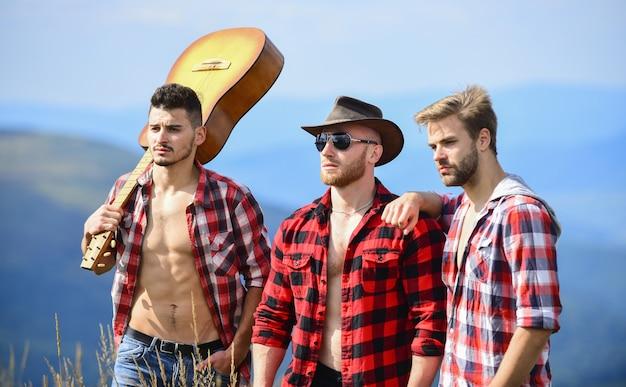 ギター奏者。人々のグループは一緒に自由な時間を過ごします。ハイキングの冒険。カウボーイの男性。西部のキャンプ。キャンプファイヤーの歌。ギターと幸せな男性の友達。友情。市松模様のシャツのギターを持つ男性。