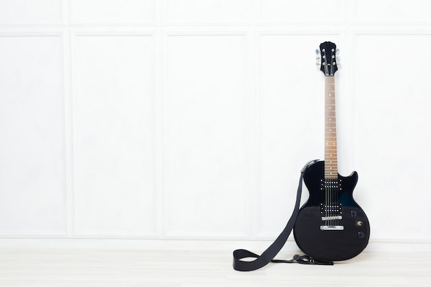 Guitar propped in front of a white wall