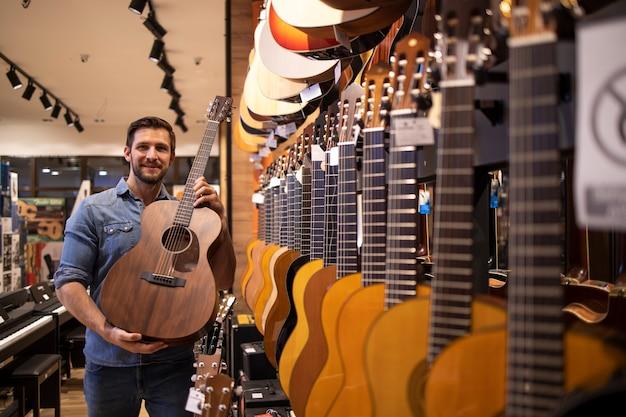Продавец гитары показывает новую модель гитары в музыкальном магазине.