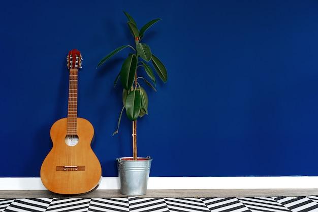 アパートのクラシックな青い壁に対するギターのセットアップ