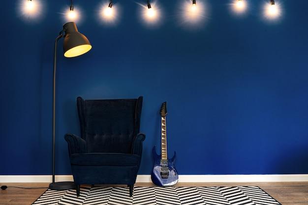 Установка гитары на фоне классической синей стены в квартире