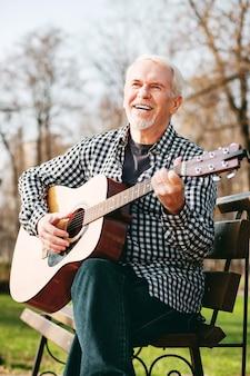 Звук гитары. низкий угол веселого зрелого мужчины, смеющегося и играющего на гитаре