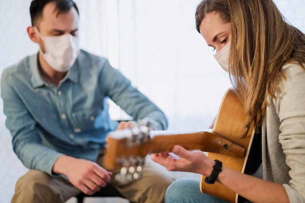 Guitar teacher overseeing woman learning how to play