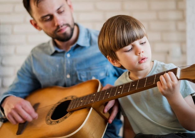 Guitar teacher showing child how to play at home