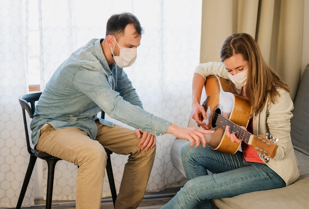 Guitar teacher showing woman how to play