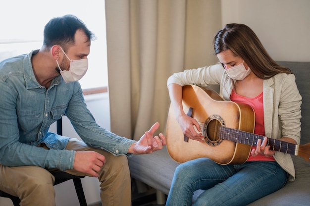 Guitar teacher tutoring woman at home