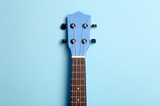 Guitar ukulele on a blue background. music playing guitar concept.
