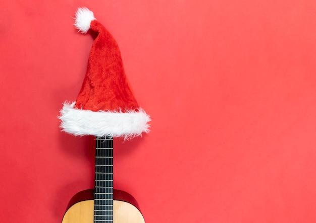 サンタクロースの帽子をかぶったギター。クリスマスソング。ハワイアンミュージック。クリスマスミュージカルフラットはコピースペースで横たわっていた。コンサートの招待状